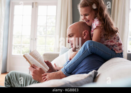 Girl on dad's shoulders while he sits reading a book at home - Stock Image