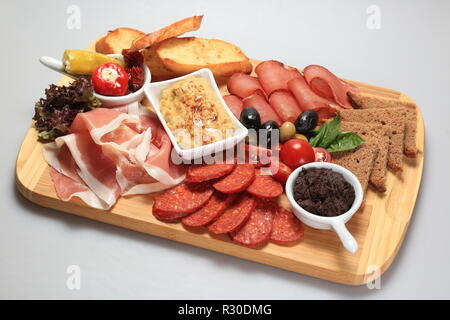 A mix of salami, cheese, ham on a plateau - Stock Image