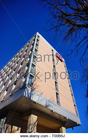 Poznan, Poland - October 31, 2018: High Mercure Hotel building with tree twigs in foreground. - Stock Image