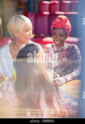 Happy young women friends drinking in sunny restaurant - Stock Image