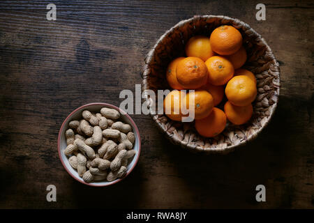overhead top view of two bowls full of peanut nuts and clementine mandarin ornages on rustic wooden table - Stock Image