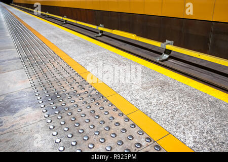 diagonal tactile paving at platform edge also called detectable warning surface to assist visually impaired pedestrians, no people - Stock Image