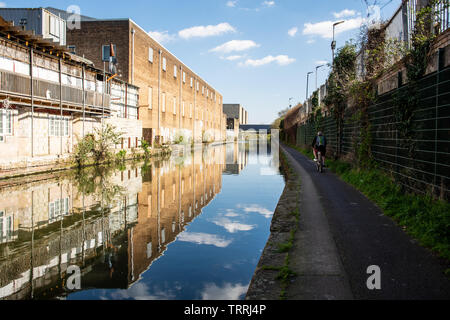 London, England, UK - March 24, 2019: A cyclist rides along the towpath of the Grand Union Canal beside industrial buildings in the Park Royal area of - Stock Image