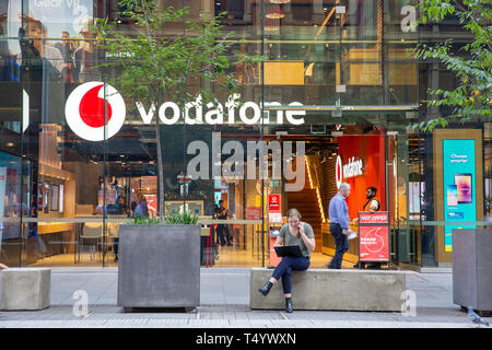 Young woman sitting outside a vodafone store in Sydney talking on her mobile phone whilst working on her laptop,Sydney,Australia - Stock Image
