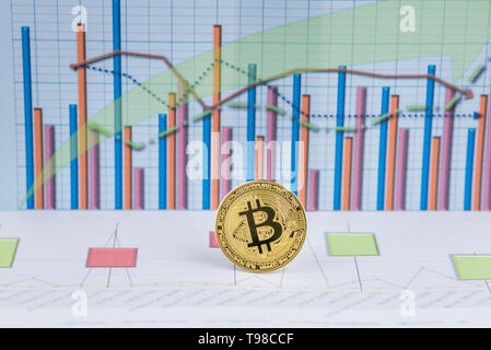 Golden Bitcoin, cryptocurrency physical coin with graph data chart . Virtual cryptocurrency concept.Concept image for cryptocurrency - Stock Image