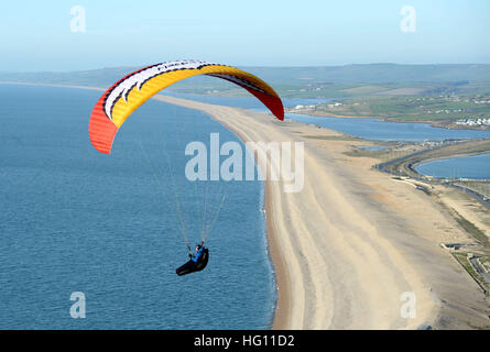 Paraglider enjoys the sunny weather off Chesil Beach, Portland in Dorset, UK - Stock Image