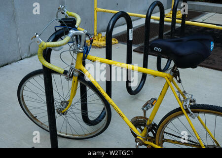 A yellow Schwinn bicycle is chained to a black, curvy bike rack - Stock Image
