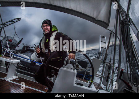 A skipper at the helm of a sailing yacht in the middle of a storm, Arctic Circle, Norway. - Stock Image