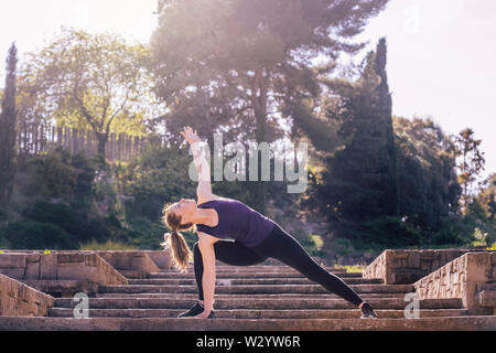 pretty young woman doing yoga exercise on the stairs of the park, morning workout outdoors, sports and healthy lifestyle - Stock Image