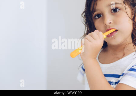 portrait of a little girl brushing her teeth in the bathroom in the morning after shower, kids hygiene concept, copy space for text - Stock Image