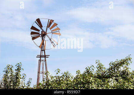 Vintage toned photo of an old western windmill tower, American wild west symbol, space for text. - Stock Image