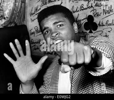 May 27, 1963; London, UK; Loud-mouthed CASSIUS MARCELLUS CLAY, the American heavyweight boxer who's voice is insured for 21, 000 pounds while he is in this country, has arrived to fight Henry Cooper. The picture shows Cassius Clay holding up five fingers to denote which he will knock out Henry Cooper in and also holdss up the first which will do the damage. - Stock Image