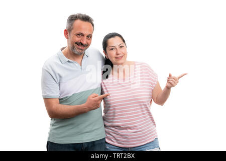 Smiling man and woman couple pointing at blank copyspace for advertising with index fingers isolated on white - Stock Image