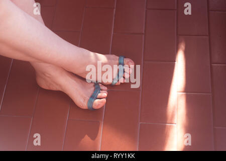 Young woman with silicone toe separator to separate toes to pedicure and paint or file toenails. - Stock Image