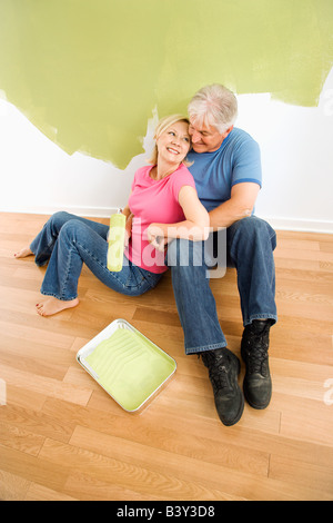 Portrait of happy adult couple sitting in front of half painted wall with paint supplies snuggling - Stock Image