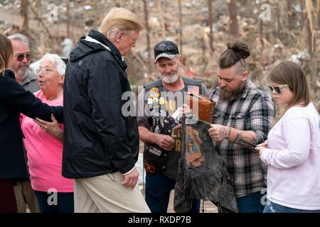 Opelika, Alabama, USA. 08th March, 2019. Survivors show U.S President Donald Trump a bible and other belongings that were left behind by a tornado as meets with residents and views the damage March 8, 2019 in Opelika, Alabama. The region was hit by a tornado on March 3rd killing 23 people. Credit: Planetpix/Alamy Live News - Stock Image