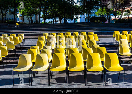 Many yellow chairs in a row on a stone pavement in the centre of the city. - Stock Image
