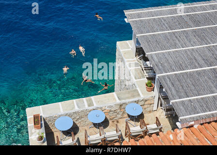 People enjoy the sun and crystal turquise sea at Hydra island - Stock Image