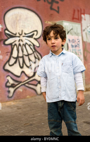portrait of a young boy in front of a wall with graffiti of a skull - Stock Image