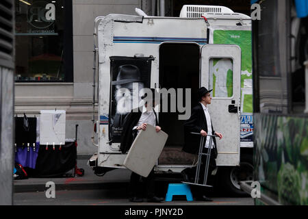 New York, United States of America. 07rd, Sep 2018.  A Mitzavah tank vehicle park in Wall Street area with a group of Jewish Orthodox works chippers, is dedicated to the Lubavitcher Rebbe (Rabbi Menachem.M Scheneersho, he was the founder of the Mitzvah Tank in 1974.  The vehicle is used by the group as a portable educational and outreach center and mini -synagogue to reach out to non observant and alienated Jews. in New York, United States of America, 07 September 2018. (PHOTO) Alejandro Sala/Alamy News - Stock Image