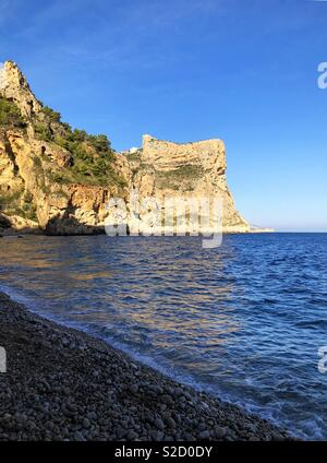 Cala del Moraig and dramatic sea cliffs in late afternoon sunlight, near Benitachell on the Costa Blanca, Spain - Stock Image