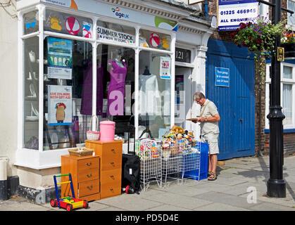 Man outside Age Concern charity shop, England UK - Stock Image