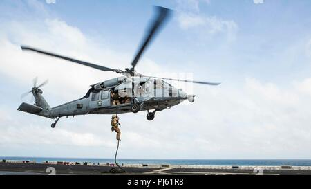 INDIAN OCEAN – U.S. Marine Lance Cpl. Alexander Huynh, a rifleman with Lima Company, Battalion Landing Team (BLT) 3/1, 13th Marine Expeditionary Unit (MEU), fast-ropes out of an MH-60S helicopter aboard the Wasp-class amphibious assault ship USS Essex (LHD 2), September 2, 2018.  Essex is the flagship for the Essex ARG and, with the embarked 13th MEU, is deployed to the U.S. 5th Fleet area of operations in support of naval operations to ensure maritime stability and security in the Central Region, connecting the Mediterranean and the Pacific through the western Indian Ocean and three strategic - Stock Image