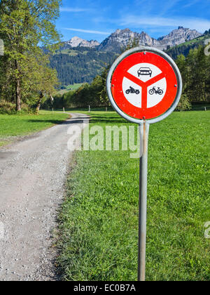 A roadsign on a gravel road running along an alpine valley,  forbidding entry for motorised vehicles - Stock Image