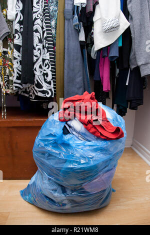 Bag of clothes taken out of a closet, ready to be donated or given away - Stock Image