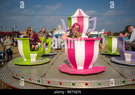 Families enjoying a ride on a teacup fairground roundabout at an agricutural show near Henley-on-Thames, Oxfrdshire. - Stock Image