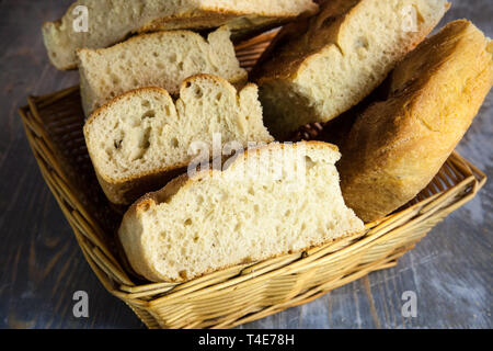 Italian bread of Focaccia Genovese type on display on a basket on a rustic wooden table, sliced in several squared pieces. The focaccia is a tradition - Stock Image