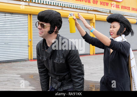 A Chinese Elvis impersonator uses hairs[pray on a Lebanese impersonator prior to  the annual Polar Bear Club New Year's day swim in Coney Island, NYC - Stock Image