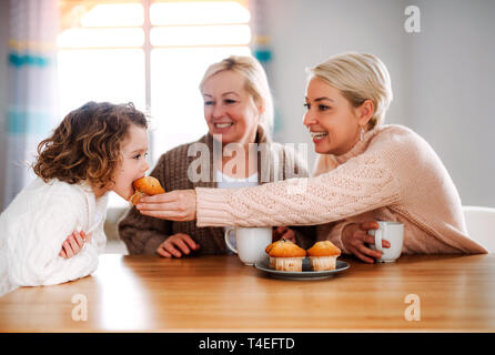 A portrait of happy small girl with mother and grandmother sitting at the table at home, eating muffins. - Stock Image