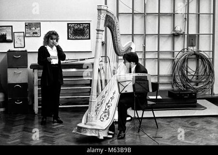Male harpist practicing in school gym using concert harp at small eisteddfod in village hall Talsarnau Gwynedd Wales - Stock Image