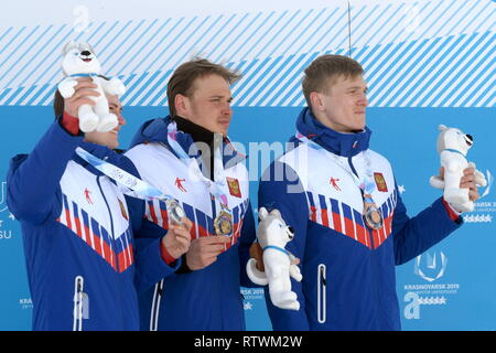 Krasnoyarsk, Russia. 03rd Mar, 2019. KRASNOYARSK, RUSSIA - MARCH 3, 2019: Russian skiers Anton Timashov (silver), Ivan Yakimushkin (gold), and Ivan Kirillov (bronze), from left, at a victory ceremony for the men's 10km cross-country skiing race during the 2019 Winter Universiade. Alexei Druzhinin/Russian Presidential Press and Information Office/TASS Credit: ITAR-TASS News Agency/Alamy Live News - Stock Image