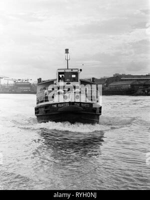 Mid Tyne ferry, Tyne Princess, with river Tyne factories and  cranes in background, early 1970s, north east England, UK - Stock Image