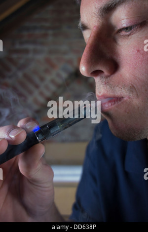 Male breathing in the vapor from an electronic cigarette - Stock Image