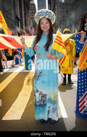 A beautiful Vietnamese American woman in a traditional AO DAI dress at the Vietnamese American Cultural Parade in Midtown Manhattan, New York City. - Stock Image