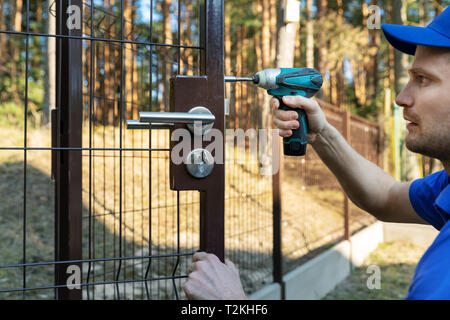 worker installing the lock for new metal fence gates - Stock Image