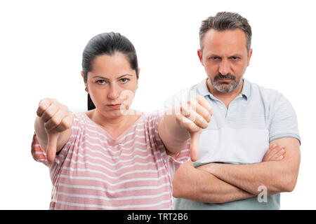 Angry woman making double thumbs-down dislike gesture and man with crossed arms behind as couple concept isolated on white - Stock Image