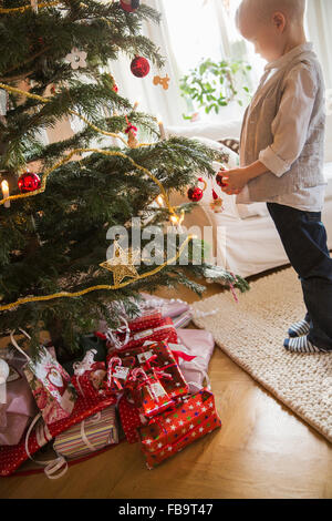 Sweden, Little blonde boy (4-5) standing next to Christmas tree - Stock Image