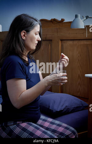 Middle aged woman in pajamas sitting on the side of her bed taking an antidepressant or sleeping pill, vignette - Stock Image