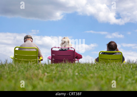 Family enjoying recreation - relaxing in the park against a clear blue sky. - Stock Image