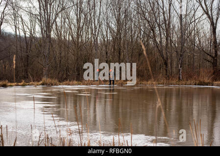 Two people stand next to a frozen pond in winter in Pennsylvania. - Stock Image