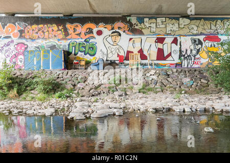 Freiburg graffiti and homeless possessions underneath road next to river - Freiburg im Breisgau, Germany, Europe - Stock Image