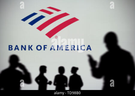 The Bank of America logo is seen on an LED screen in the background while a silhouetted person uses a smartphone in the foreground (Editorial use only - Stock Image