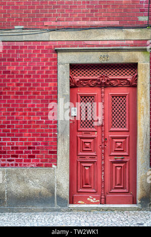 Ornate red door in a red tiled builing in Porto, Portugal. - Stock Image