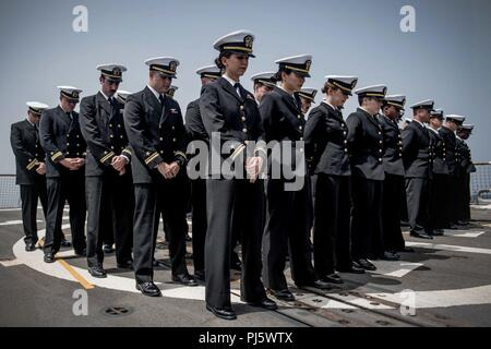 180825-N-UX013-1091 U.S. 5TH FLEET AREA OF OPERATIONS (Aug. 25, 2018) Sailors bow their heads in prayer during a memorial ceremony at sea for Ensign Sarah Mitchell aboard the guided-missile destroyer USS Jason Dunham (DDG 109). Dunham is deployed to the U.S. 5th Fleet area of operations in support of naval operations to ensure maritime stability and security in the Central Region, connecting the Mediterranean and the Pacific through the western Indian Ocean and three strategic choke points. (U.S. Navy photo by Mass Communication Specialist 3rd Class Jonathan Clay/Released) - Stock Image