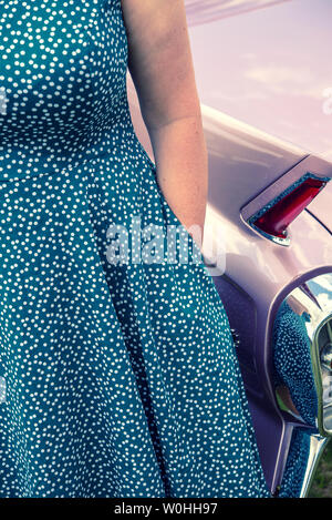 Woman in a 1950s style dress standing in front of a vintage American Cadillac - Stock Image