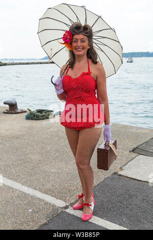 Poole, Dorset, UK. 14th July 2019. Poole Goes Vintage Event takes place on the Quay for a day of vintage music, dance, fashion, memorabilia, entertainment, vehicles and stalls on a 1940's and 1950's theme, including Lindy Hop and Jive on Poole Quay. Thousands turn out to watch, listen and take part. Helen in her red polka dot swimsuit and shoes, with parasol, gloves and case. Credit: Carolyn Jenkins/Alamy Live News - Stock Image